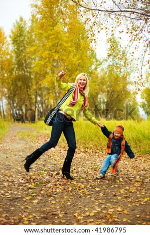 happy young beautiful mother and her son  have a walk in the park