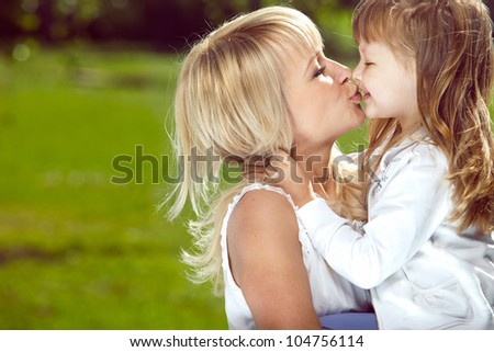 Happy young beautiful mother with smiling daughter outdoors