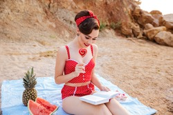 Happy young beautiful pin up girl reading a book and holding heart shaped candy