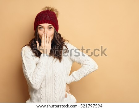 Happy Young Beautiful Woman in winter clothes Surprised on soft background with copy space. Sales and discount concept