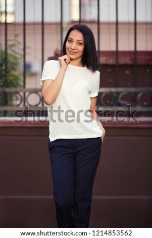 Happy young beautiful woman walking in city street Stylish fashion model wearing white t-shirt and dark blue pants