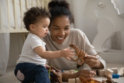 Happy young biracial mom lying on floor play with small curious ethnic baby infant at home. Smiling loving African American mother engaged in funny activity with small infant child. Childcare concept.