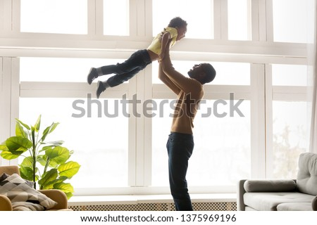 Happy young black father lifting up in air holding raise hands little son excited family playing active games having fun stands in living room near window people spending time together at home concept