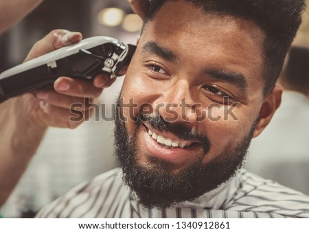 Happy young black man being trimmed with electric clipper machine in barbershop.Male beauty treatment concept.Smiling young African guy getting new haircut in barber salon.Portrait of barbers client