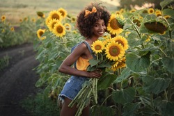 Happy young black woman in a sunflower field. Smiling dark-skinned girl with with a bouquet of sunflowers and curly hair.