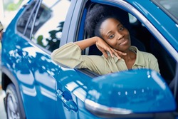 happy young black woman in dealership, beautiful lady came to buy automobile,she liked one of cars represented in dealership
