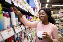 Happy young black woman shopping in beauty department of big supermarket, choosing personal care products. Lovely African American lady buying goods at hygiene section of mall