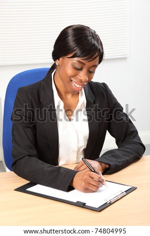 Happy young black woman working in office sitting to her desk signing a document. Picture taken from high angle.