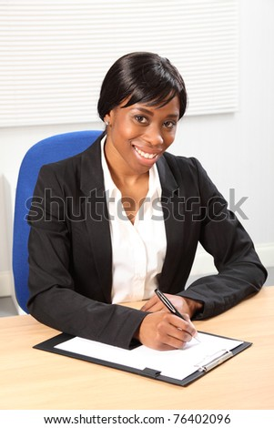 Happy young black woman working in office sitting to her desk signing a document. She is looking up from signing a paper document with a beautiful smile. Picture taken from high angle.