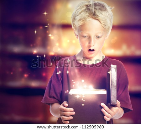 Happy Young Blond Boy Opening a Gift Box