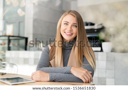 Happy young blond busineswoman in smart casualwear sitting by table in modern cafe in front of camera
