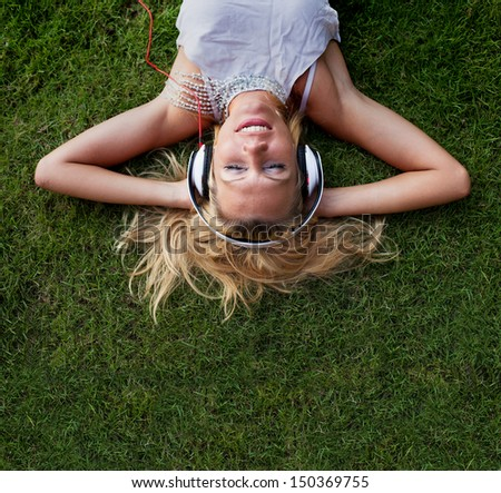 happy young blond woman in headphones on the grass