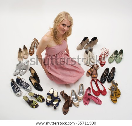 happy young blond woman sitting on the floor surrounded by shoes