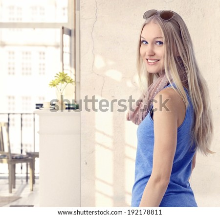 Happy young blonde casual caucasian woman at vintage home. Looking back at camera, smiling, standing, sunglasses.