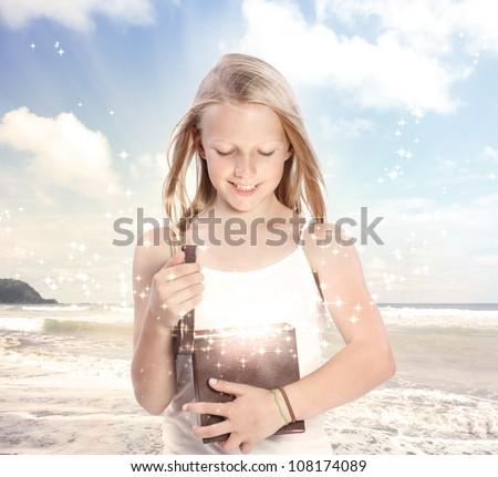 Happy Young Blonde Girl Opening a Gift Box on the Beach