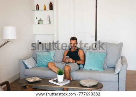 Happy young blonde man sitting in the couch at home on the mobile phone