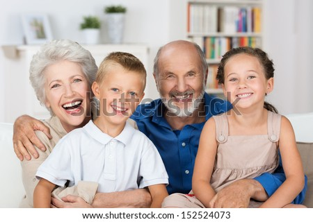 Happy Young Boy And Girl With Their Laughing Grandparents Smiling At The Camera As They Pose Together Indoors