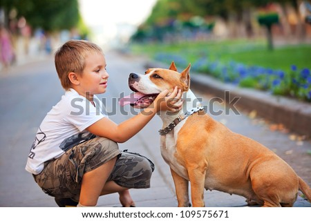 Happy young Boy and his dog in summer street