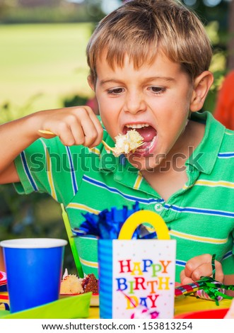 Happy Young Boy Eating Cake at Birthday Party