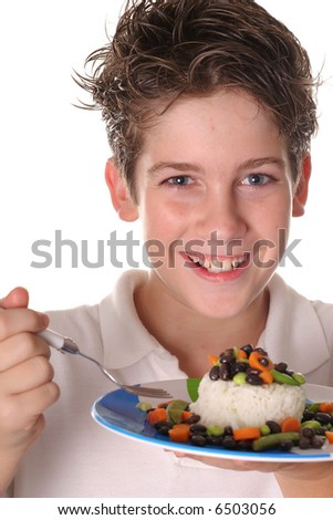 happy young boy eating healthy rice, beans & veggies vertical