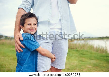 Happy young boy hugging his dad and smiling in the park