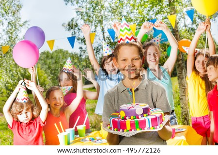 Happy young boy in party hat holding birthday cake #495772126