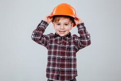 Happy Young boy in shirt holding to the helmet and looking at camera. Isolated gray background