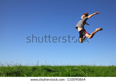 Happy young boy jumping in the meadow
