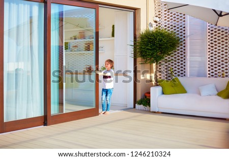 happy young boy, kid opening the sliding door on rooftop patio area at home ストックフォト ©
