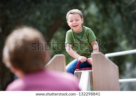 Happy young boy playing on a playground teeter totter