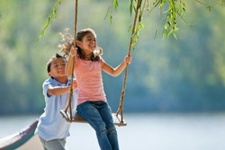 Happy young boy pushing a young girl on a tree swing.