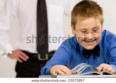 Happy young boy reading a magazine with father on background