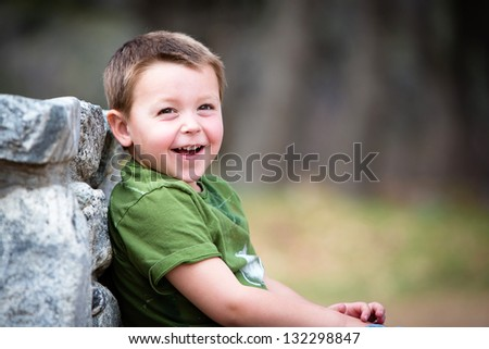 Happy young boy sitting outdoors laughing