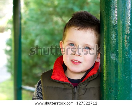 Happy young boy smiling in an outdoor scene