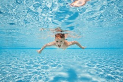 Happy young boy swim and dive underwater, kid breast stroke with fun in pool. Active healthy lifestyle, water sport activity and lessons with parents on summer family vacation with child.
