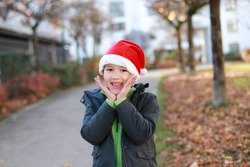 Happy young boy wearing red Santa Claus hat laughing on outdoor background. Mixed race Asian-German kid concept for merry Christmas and happy new year celebration.funny child surprised and exited face