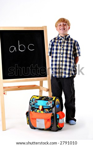 Happy young boy with his school bag next to a black board.
