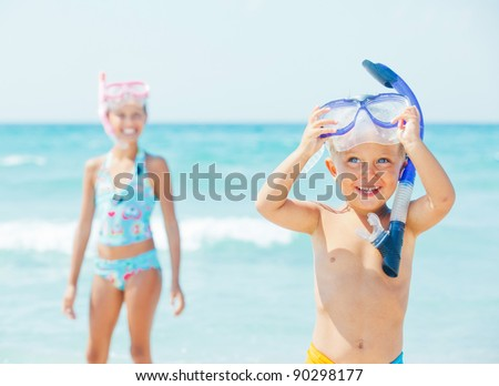 Happy young boy with snorkeling equipment on sandy tropical beach, his sister background.