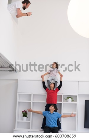happy young boys having fun and posing line up piggyback in new modern home #600708659