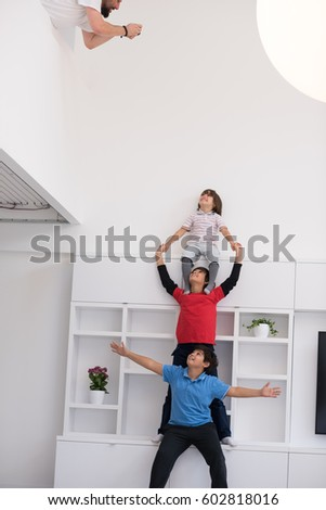 happy young boys having fun and posing line up piggyback in new modern home #602818016