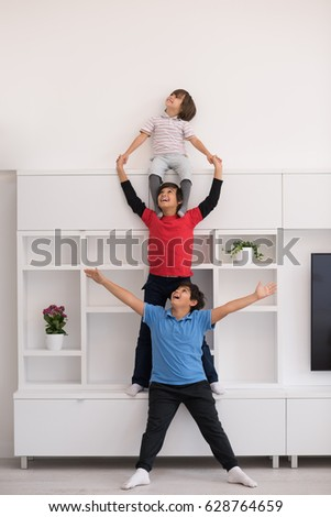 happy young boys having fun and posing line up piggyback in new modern home #628764659