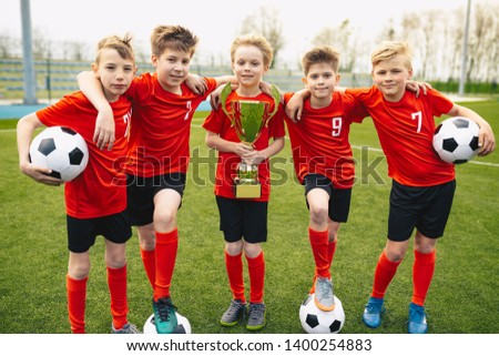 Happy Young Boys In Football Team. Kids in School Soccer Sports Team Holding Golden Trophy and Soccer Balls. Group Of Children In Soccer Team Having Fun After Winning Final Tournament Game #1400254883