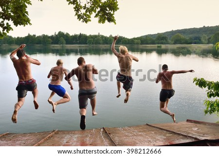 Happy young boys jumping togetherto the calm summer sea, adventure team photo on summer holiday or vacation, summer memories, original wallpaper full of happiness and energy