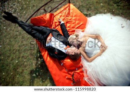 Happy young bride and groom lie on a bed with a red blanket outdoors