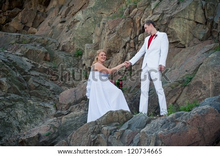 Happy young bride and groom outside on the mountain on their wedding day - Copyspace. Wedding couple - new family! wedding dress. Bridal wedding bouquet of flowers