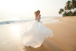 Happy young bride woman in white dress  running, have fun on clean sandy beach waves of azure sea or ocean on sunset, summer vacation at water. Wedding rest, relax honeymoon concept.