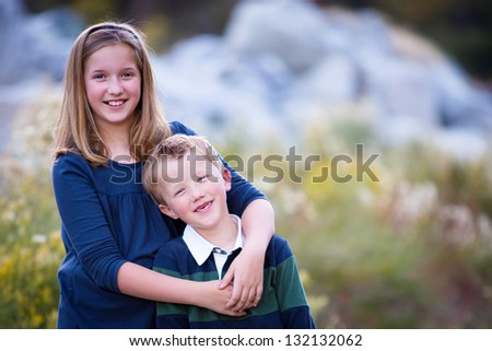 Happy young brother and sister snuggling close in a beautiful outdoor setting