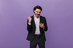Happy young brunette-haired man in white shirt and black striped suit emotionally looking at phone, rejoicing and posing against violet pastel background