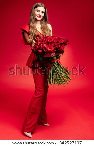 Happy young brunette in red dress holding big bunch of red roses.