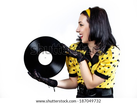 Happy young brunette in retro style with a vinyl record